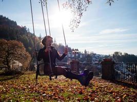 una ragazza sta oscillando su un'altalena. giorno soleggiato. foto