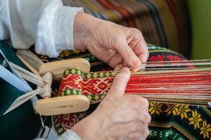 donna che lavora al telaio per tessitura. artigianato etnico tradizionale del Baltico. - Immagine foto