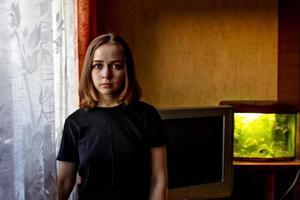 ritratto di una giovane ragazza adolescente in una stanza vicino alla finestra la sera foto