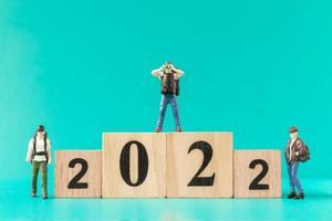 zaino in spalla in miniatura e turista in piedi sul blocco di legno numero 2022 foto