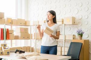 imprenditore di una donna asiatica che lavora a casa con una scatola di imballaggio sul posto di lavoro - imprenditore di PMI dello shopping online o concetto di lavoro freelance foto