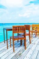tavolo e sedia in legno per esterni vuoti con sfondo vista mare alle maldive foto
