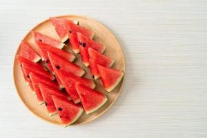 Anguria fresca affettata su piatto di legno foto