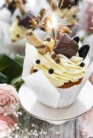 cupcakes al cioccolato con stelle filanti su fondo di legno bianco foto