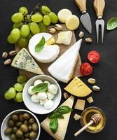 vari tipi di formaggio, uva, miele e snack foto