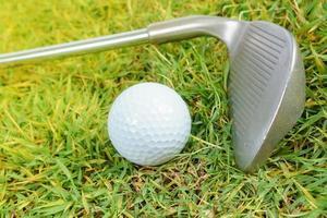 mazze da golf e pallina da golf su sfondo verde erba green foto