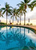 ombrellone e sedia intorno alla piscina nel resort dell'hotel con l'alba al mattino foto