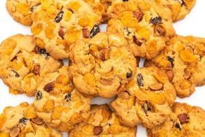 Biscotti fatti in casa con uvetta cornflake e mandorle isolati su sfondo bianco foto