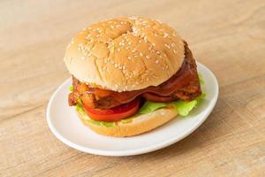 hamburger di pollo alla griglia con salsa su piatto bianco foto