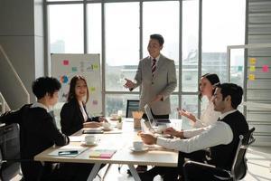 il manager asiatico discute il progetto con il team multietnico in riunione foto