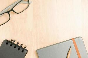 occhiali e matita marrone con taccuino su legno foto