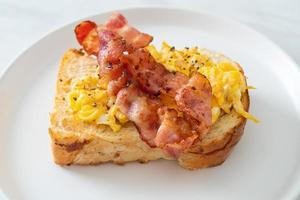 pane tostato con uova strapazzate e pancetta su piatto bianco foto