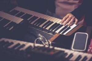 musicista che suona una tastiera di synth vintage foto