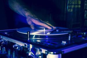 mani di un dj durante la riproduzione di dischi in vinile a una festa foto