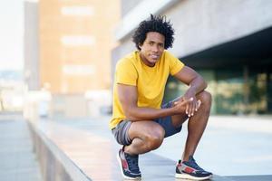 uomo di colore con i capelli afro che si prende una pausa dopo l'allenamento. foto