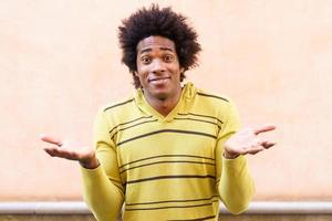 uomo di colore con i capelli afro che mette un'espressione divertente foto