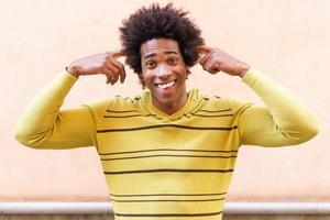 uomo di colore con i capelli afro che fa un'espressione pazza foto