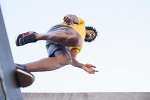 vista dal basso dell'uomo nero che salta sulla sua corsa. foto
