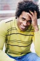 turista cubano nero con i capelli afro seduto sul pavimento foto