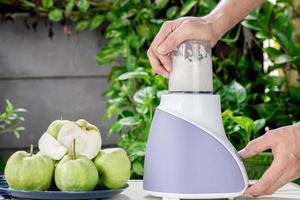 usando un frullatore elettrico per fare il succo di guava fresco foto