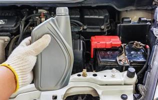 meccanico auto mano che tiene olio motore, manutenzione auto foto