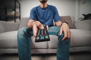 uomo tenere premuto e premere il pulsante del telecomando del televisore. foto
