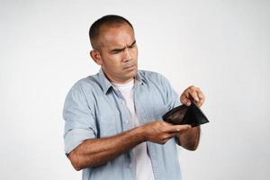 uomo maturo sconvolto che tiene e guarda dentro il suo portafoglio vuoto. senza soldi foto