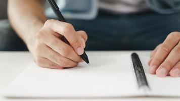 primo piano delle mani dell'uomo che scrivono sul blocco note, taccuino usando la penna. foto