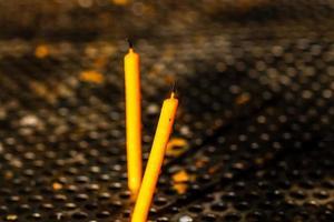 candele accese che si sciolgono in memoria dei morti, primo piano. foto