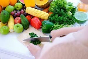 mani usando un coltello tritare verdura su tavola da intaglio in legno sul tavolo a tenda bianca sullo sfondo curtain foto