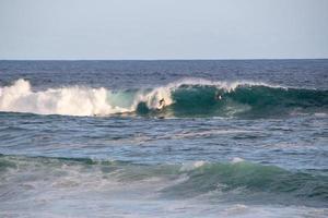 surfisti che cavalcano un'onda sulla spiaggia di arpoador a rio de janeiro, brasile foto