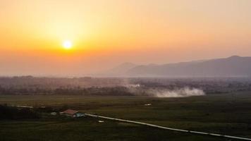 paesaggio al tramonto cielo arancione e sagome di colline sullo sfondo foto