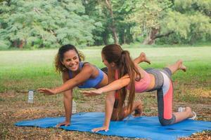 donne fitness che praticano yoga in un parco. donne che fanno allenamento fitness in un parco. foto