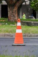 cono di segnalazione arancione con strisce bianche foto
