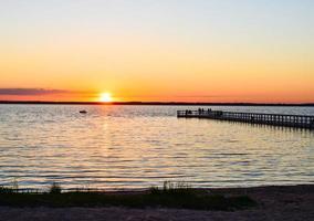 lago rekyva con molo e persone che guardano il tramonto. viaggio turistico in siauliai, lituania. foto