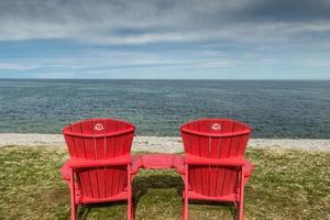 sedie rosse con vista sul fiume San Lorenzo dalle navi ruscello. parco nazionale del gros morne, terranova, canada foto