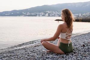 giovane donna che medita sulla spiaggia foto