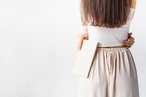 donna su sfondo bianco con in mano un libro, vista da dietro foto