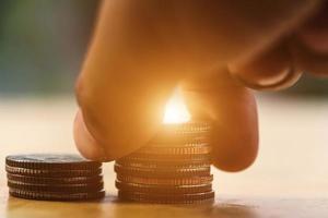 mano che mette la moneta da impilare con il concetto di risparmio di denaro foto