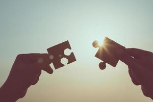 silhouette di mani in primo piano che tengono il collegamento puzzle jigsaw foto