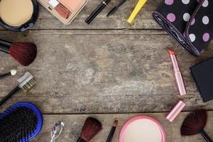 cosmetici e pennelli per il trucco sullo sfondo del tavolo in legno foto