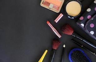 cosmetici per il trucco e pennelli su sfondo nero foto