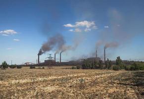 fumare pipe di fabbrica contro un cielo blu e nuvole foto