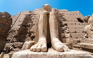 piedi di un'antica statua del faraone nel tempio di Karnak a Luxor foto