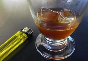 caffè con ghiaccio e accendino sul tavolino della terrazza foto