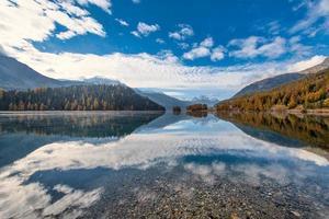 paesaggio di montagna con un lago dove si riflettono le nuvole foto