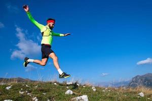 skyrunner durante un salto in discesa nei prati di montagna foto