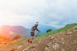 atleta skyrunner mentre si allena in montagna con i bastoni foto