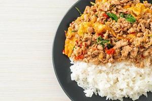 maiale macinato saltato in padella con basilico e uova ricoperte di riso - stile asiatico foto