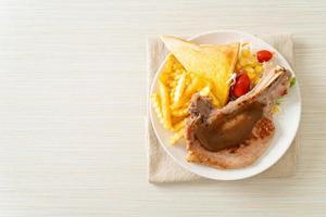 bistecca di braciola di maiale con patatine e mini insalata su piatto bianco foto